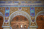 Arabesque Mudjar plasterwork and arches of the 12th century Salón de Embajadores (Ambassadors' Hall or Throne Room). Alcazar of Seville, Seville, Spain . The Royal Alcázars of Seville (al-Qasr al-Muriq ) or Alcázar of Seville, is a royal palace in Seville, Spain. It was built by Castilian Christians on the site of an Abbadid Muslim alcazar, or residential fortress.The fortress was destroyed after the Christian conquest of Seville The palace is a preeminent example of Mudéjar architecture in the Iberian Peninsula but features Gothic, Renaissance and Romanesque design elements from previous stages of construction. The upper storeys of the Alcázar are still occupied by the royal family when they are in Seville. <br /> <br /> Visit our SPAIN HISTORIC PLACES PHOTO COLLECTIONS for more photos to download or buy as wall art prints https://funkystock.photoshelter.com/gallery-collection/Pictures-Images-of-Spain-Spanish-Historical-Archaeology-Sites-Museum-Antiquities/C0000EUVhLC3Nbgw <br /> .<br /> Visit our MEDIEVAL PHOTO COLLECTIONS for more   photos  to download or buy as prints https://funkystock.photoshelter.com/gallery-collection/Medieval-Middle-Ages-Historic-Places-Arcaeological-Sites-Pictures-Images-of/C0000B5ZA54_WD0s