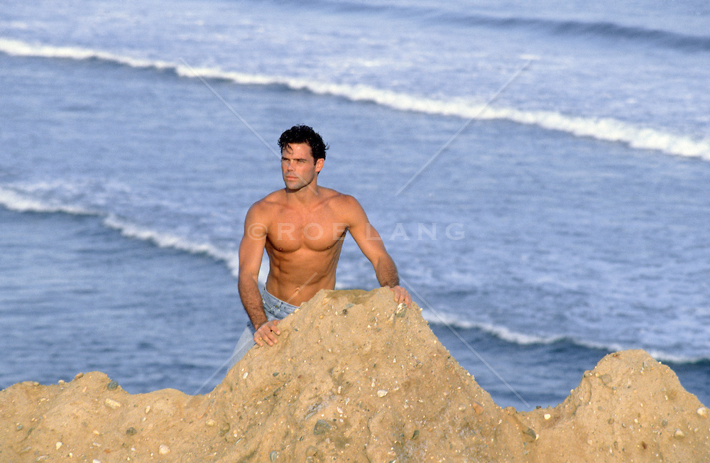 shirtless man standing on a cliff above the Atlantic Ocean in Montauk, NY