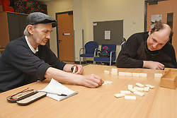 Men with disabilities playing dominoes at a resource for people with physical and sensory impairment.