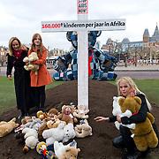 """Amsterdam, 01-12-2013. Rouwende knuffels op het Museumplein Amsterdam. STOP AIDS NOW voert vandaag 1 december - Wereld Aids Dag - actie voor 2,6 miljoen kinderen met hiv die nog geen behandeling met hiv-remmers krijgen. Op het Museumplein rouwt vandaag een reusachtige knuffelbeer van acht meter naast een symbolisch graf. Ambassadeurs Angela Groothuizen en Nicolette Kluijver alsmede Puck - winnares Comedy Kids - leggen knuffelberen om het graf dat symbool staat voor alle kinderen die in 2013 overleden aan de gevolgen van aids. De knuffels dragen een label met de boodschap:""""Ieder jaar verliezen 160.000 knuffels in Afrika hun vriendje aan de gevolgen van aids. Zonder behandeling wordt de helft van alle kinderen met hiv in Afrika niet ouder dan twee jaar""""."""