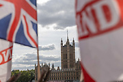 TheHouses of Parliament with a Union Jack and St Georges Cross flag in the foreground on the 29th August 2019 in London in the United Kingdom.