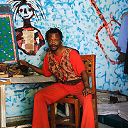 """Psychiatric patient, Samuel, believes he is Emperor Haile Selassie I of Ethiopia. He painted the walls of his room himself, and says the figure on the wall next to him is his """"spiritual interlocutor"""". He says he was inspired to paint the guitar after he saw God, who was walking towards him """"playing a guitar in a rasta style."""" Local lore has it that he fell ill after marrying a girlfriend in the underworld."""