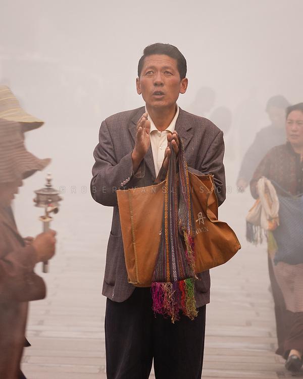 Praying man at Barkhor Square, Lhasa, Tibet, China. Photo ©robertvansluis.com