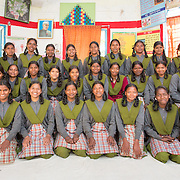 CAPTION: Class photo at Mahila Samakhya's residential school in Ratu, Ranchi. Mahila Samakhya takes on young women who've been abandoned or sexually abused, and teaches them with a view to mainstreaming them back into society, including the area of sexual and reproductive rights. It is a national-level NGO, and is working in 11 districts in Jharkhand. Last year, EngenderHealth worked with the Government to bring Mahila Samakhya into the Rashtriya Kishor Swasthya Karyakram (RKSK) (National Adolescent Health Program). LOCATION: Mahila Samakhya, Ratu (block), Ranchi (city), Jharkhand (state), India. INDIVIDUAL(S) PHOTOGRAPHED: Adults: Malti Laguri (left) and Rajni Lakra (right); children: multiple people.