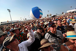 25 April 2014. New Orleans, Louisiana.<br /> A ball floats through the crowd gathered to hear Carlos Santana at the New Orleans Jazz and Heritage Festival. <br /> Photo; Charlie Varley/varleypix.com