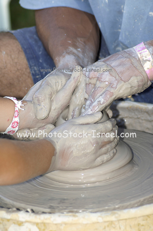 Potter teaching a child to make a clay pot