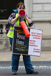 London, UK. 15th July, 2021. A campaigner stands in front of Downing Street with a loud hailer during a protest by leaseholders and tenants living in unsafe homes. Some leaseholders are faced with crippling costs to fix safety issues and they called on the government to ensure that their homes are made safe from fire as a matter of priority, to make interim payments and cover fire safety remediation costs and to find a solution with mortgage lenders.