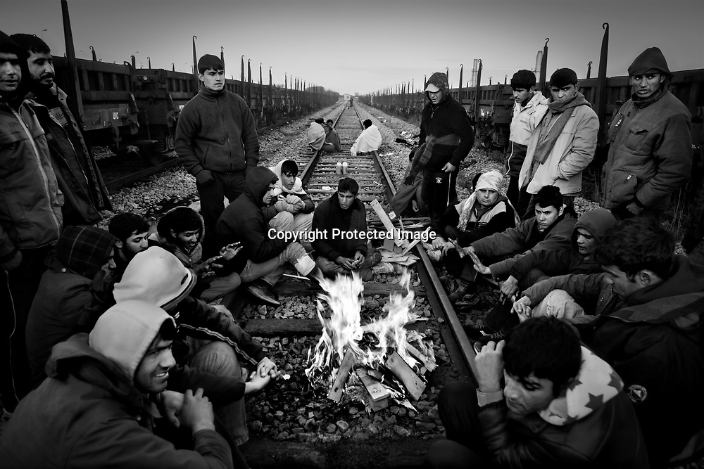 Evening in the 'Jungle'. The migrants gather around the fire to keep warm.