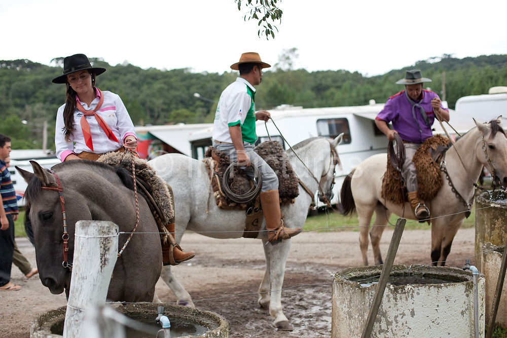 Young Brazilian Gauchas cowgirls females and Gaucho cowboy males, riding horses, preparing to compete in a rodeo. Gaucho cowboy Rodeo, Flores de Cunha, Rio Grande do Sul.