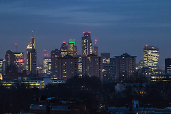 Primrose Hill, London, January 12th 2017. Dawn breaks over London, seen from Primrose Hill, as the South East of England braces itself for rain and possibly snow later in the day. PICTURED: The city skyline, its skyscrapers still lit up, emerges from the darkness.
