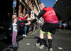 A competitor shakes hands with competitors during the 2019 London Landmarks Half Marathon.