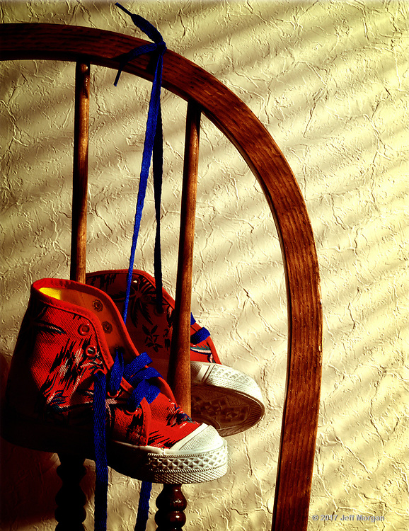 Still life image of colorful kids sneakers on the back of a chair.