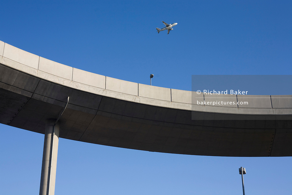A jet airliner climbs away as it takes-off over a traffic ramp at Heathrow Airport's Terminal 5.