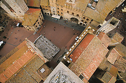 Europe, Italy, Tuscany, San Gimignano, tile roofs and plaza viewed from top of 13th century tower. UNESCO World Heritage Site