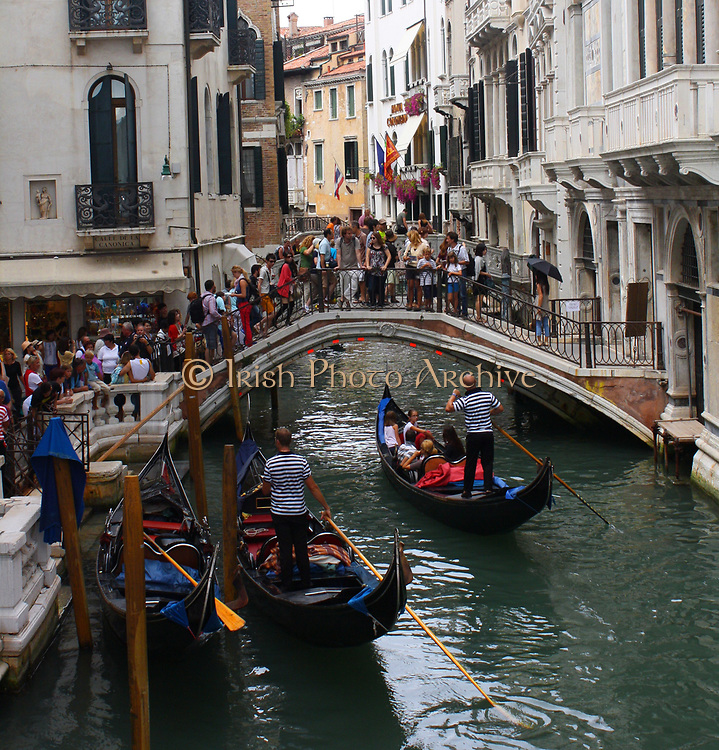 Bridge and Boat Scene 2013. A busy scene showing Gondolas, The Grand Canal and people crossing a bridge.