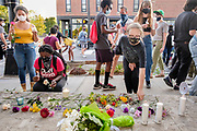 "20 AUGUST 2020 - DES MOINES, IOWA: People lay flowers and candles at an impromptu memorial for missing Black children. About 150 people, members of and supporters of Des Moines Black Liberation Movement (which used to be known as Black Lives Matter) marched through a residential neighborhood of Des Moines Thursday night demanding justice for Black children. The march was called to show support for Breasia Terrell and  Abdullahi ""Abdi"" Sharif, two Black children who went missing in Iowa this year. Terrell, a 10 year old girl,  went missing on July 10 and is still missing. Sharif, a teenager, disappeared from a Des Moines shopping mall in January, his body was found in May. Members of BLM said authorities have not adequately investigated the disappearances.     PHOTO BY JACK KURTZ"