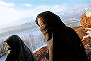 Fatemah, 12, (Right) and her mother, Maryam, 38, (Left) are sitting in front of the cave where they live since seven years, during a cold winter morning in Bamyan, central Afghanistan, an area mostly populated by Hazaras. A historically persecuted minority (15%) due to more lenient Islamic faith and characteristic 'Eastern' lineaments, Hazaras constitute the 70% of Bamyan's population.