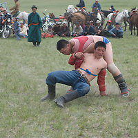 MONGOLIA. Nomadic herders wrestle at a naadam festival on a remote pass in Arbulag Sum, near Muren in Hovsgol Aimag, Mongolia. This ancient sport is immensely popular across the country, and legend says that men wear their unique costumes to prove that they are not women, after a woman once humiliated male wrestlers by beating them.