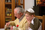 Grandfather and grandson reading the Haggadah at the Passover table. Model Release Available