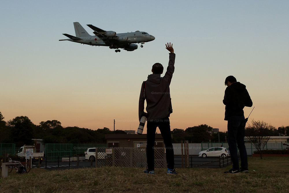 Military aircraft enthusiasts wave at a  Kawasaki P1 Maritime patrol aircraft, with the JSDF.  as it lands at Atsugi Airbase in Yamato, Kanagawa, japan. Friday November 2nd 2018