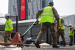 © Licensed to London News Pictures. 10/04/2020. Manchester, UK. Soldiers from the 1st Battalion the Duke of Lancaster's Regiment assemble the first beds to arrive in the hospital . The National Health Service is building a 648 bed field hospital for the treatment of Covid-19 patients , at the historical railway station terminus which now forms the main hall of the Manchester Central Convention Centre . The facility is due to open next week and will treat patients from across the North West of England , providing them with general medical care and oxygen therapy after discharge from Intensive Care Units . Photo credit: Joel Goodman/LNP