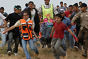 Palestinian youths and paramedics carry an unidentified injured youth from the clash between Israeli tanks and the youths in Beit Lahia in Gaza Strip, the border city of three Jewish settlements including Eily Senai.