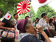 August 16, 2017, Tokyo, Japan: With her harmonica, this elderly women leads a nostalgic group in the singing WW II era patriotic songs. This was part of the festivities taking place at Yasukuni Shrine on the 72nd anniversary of the end of WW II. Here, tens of thousand came out in the rain to pay their respects for Japan's war dead. Yasukuni Shrine is the national Shinto shrine where nearly 2.5 million war dead from the past 150 years are enshrined. Visits to Yasukuni by top Japanese politicians continue to outrage China and South Korea because it honors 14 World War II class A war criminals who are also enshrined there. Even so, dozens of Japanese lawmakers visited Yasukuni Shrine today, while PM Shinzo Abe sent a ritual offering via his emissary. Photo by Torin Boyd.