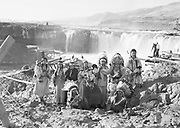 9305-B7362-4.  Indians in traditional dress at Celilo Falls. September 1938. 1= Louise Thompson. 2= Agnes Thompson. 3= either Margaret Buck or Roslene Yallup Napoleon (daughter of Hannah Yallup), 4= Hannah Sohappy Yallup (wife of Tom Frank Yallup), 5= ?child, 6= Pee-up-sun-yai (wife of William Yallup), 7= ?child, 8= Chief William Yallup, 9= ?child, 10= Henry Thompson, 11= ?child, 12= Tom Frank Yallup. Hannah Sohappy Yallup id by Amelia Sohappy on 1 Oct 1994.  . Celilo Falls, Columbia River, Oregon