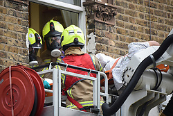 © Licensed to London News Pictures. 01/04/2020. London, UK. Firefighters wearing full respirators normally used to protect against smoke inhalation on an aerial platform at an incident involving all emergency services where a suspected COVID-19 case <br /> removed from their home. Uxbridge Road in Shepherd's Bush was closed for an hour as ambulance, fire brigade and police attended, extracting the patient by crane from a three story apartment building in West London. PPE (personal protective equipment) was in evidence, with the fire brigade using full face respirators normally reserved for firefighting. A police officer commented the Metropolitan police force are issued only with rubber gloves. Ambulance workers decontaminated the scene and reusable equipment before moving on.  Photo credit: Guilhem Baker/LNP
