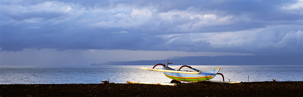 Traditional boat on beach with water glowing