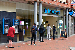 Queue for bank showing two metre markers and customer service advisor in a mask. Coronavirus pandemic, Reading UK June 2020