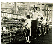 Children and overseer at work in the spinning shed of an American cotton mill, 1910.  At this date the use of child labour was widespread in US factories and in the South one quarter of the 'hands' were under sixteen.