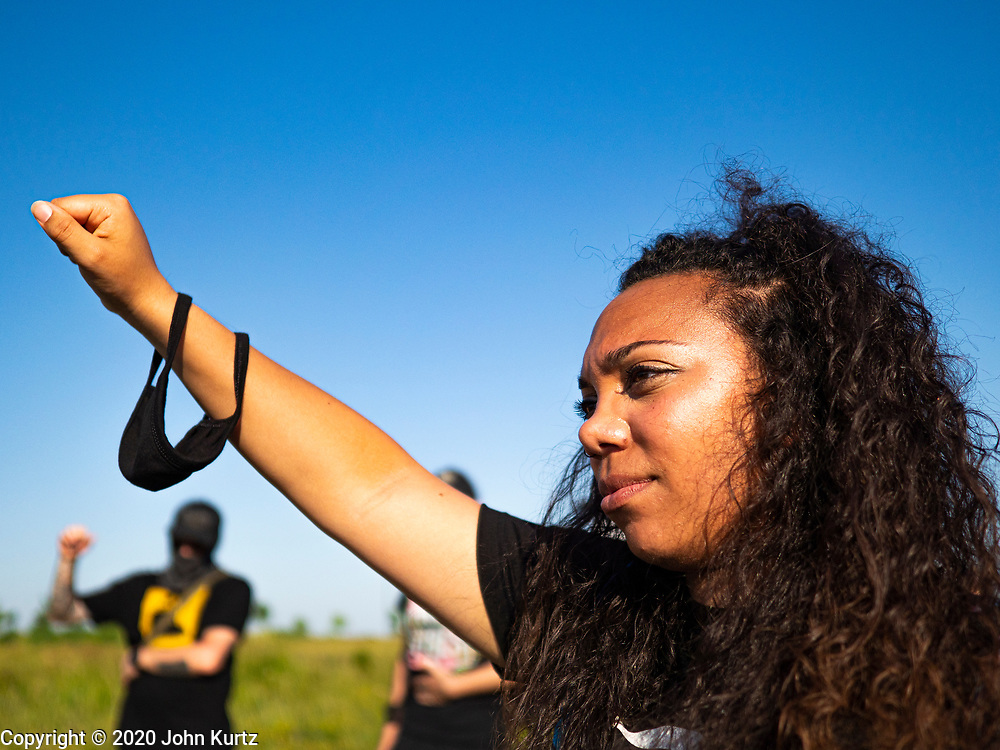 17 JUNE 2020 - NORWALK, IOWA: A member of Black Lives Matter puts her fist in the air during a protest in Elizabeth Holland Park in Norwalk. About 400 supporters of Black Lives Matter marched through Norwalk, IA, an upper class suburb of Des Moines Wednesday. Norwalk has a population of about 10,000 and, according to the US Census Bureau, is 97 percent white. The marchers were protesting police violence against people of color. The march was a reaction to the police killing of George Floyd in Minneapolis in May. The march was peaceful.        PHOTO BY JACK KURTZ