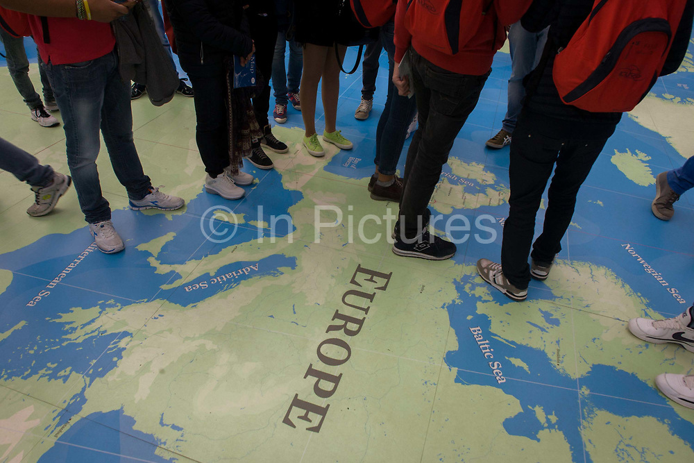 The legs and feet of students stand on a European map at the National Maritime Museum, Greenwich. The legs of  foreigners can be seen with their feet covering the countries and states of the European Union (EU) although there are no borders or political boundaries. Instead, we see the land mass of continental Europe's mainland. Also marked are names of the oceans surrounding these countries, including the Baltic, Adriatic and North Seas. The map is in London's museum that celebrates Britain's maritime history, heritage and oceanic exploration.