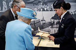 Queen Elizabeth II looks at a 1953 passenger ticket issued in her name displayed at the Heritage Centre during a visit to the headquarters of British Airways at Heathrow Airport, London, to mark their centenary year.
