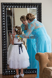 woman and little girl getting ready for a formal wedding while looking at a mirror image