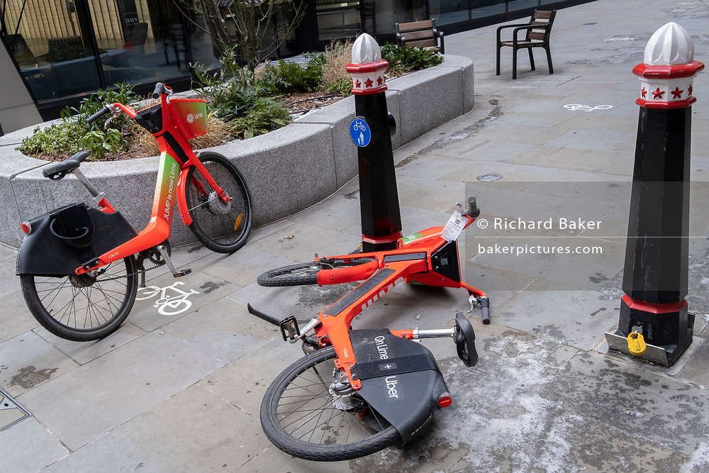 Two Uber rental bikes have been discarded by their rider, left in the middle of a deserted pedestrian street during the third lockdown of the Coronavirus  pandemic, in the City of London, the capital's financial district, on 10th February 2021, in London, England.