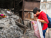 """10 AUGUST 2014 - BANGKOK, THAILAND:     A woman shields her eyes while throwing joss paper into an incinerator on the first day of Ghost Month at Wat Mangkon Kamalawat, the largest Mahayana Buddhist temple in Bangkok's Chinatown. The seventh month of the Chinese Lunar calendar is called """"Ghost Month"""" during which ghosts and spirits, including those of the deceased ancestors, come out from the lower realm. It is common for Chinese people to make merit during the month by burning """"hell money"""" and presenting food to the ghosts.PHOTO BY JACK KURTZ"""