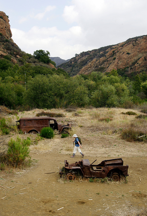 LOS ANGELES, CA, October 2, 2007: Hikers enjoy the Santa Monica Mountains by way of Malibu Creek State Park on a fall day in September, 2007. One woman walks through the MASH set where the television show was filmed. All that remains are a couple of old military jeeps.(Photo by Todd Bigelow/Aurora)