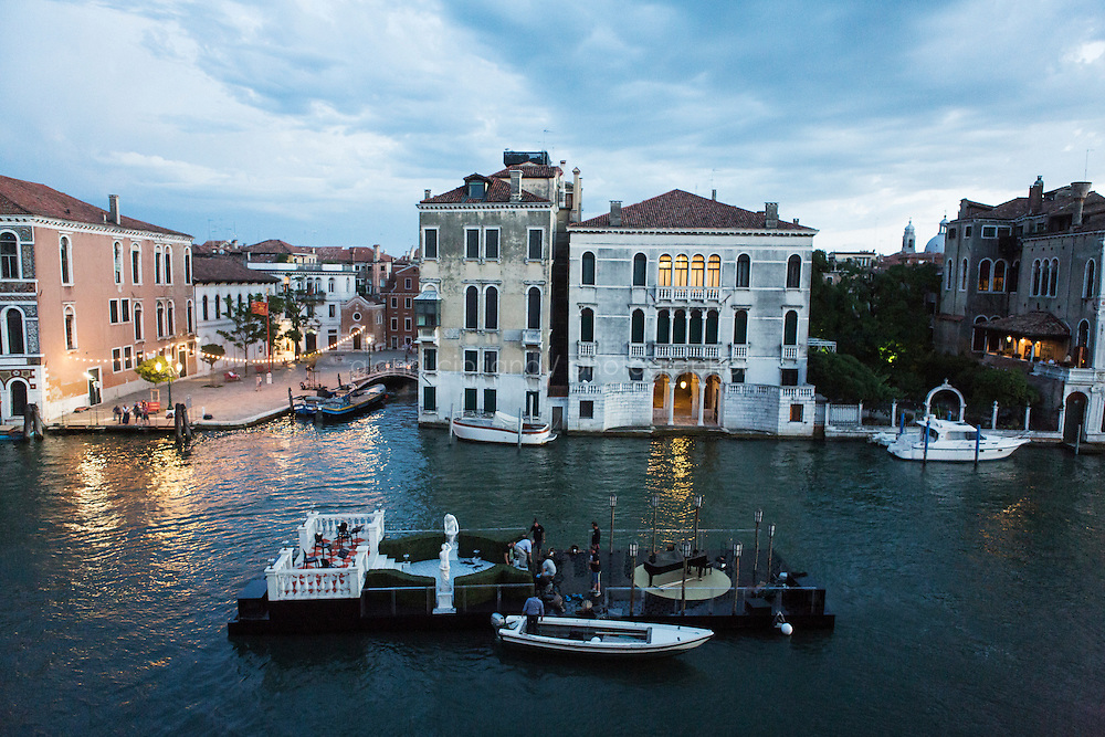 """VENICE, ITALY - 13 JULY 2016: A barge set up as the set for a scene of the third season of """"Mozart in the Jungle"""" with Gaela Garcia Bernal, Placido Domingo and Monica Bellucci, navigates in the Grand Canal in Venice, Italy, on July 13th 2016.<br /> <br /> Mozart in the Jungle is an award-winning television series produced by Picrow for Amazon Studios. The pilot was written by Roman Coppola, Jason Schwartzman, and Alex Timbers and directed by Paul Weitz. The story was inspired by Mozart in the Jungle: Sex, Drugs, and Classical Music, oboist Blair Tindall's 2005 memoir of her professional career in New York."""