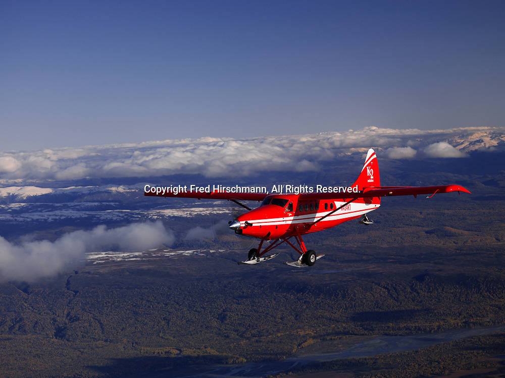 K2 Aviation's Turbo Otter on wheel skis flying from Talkeetna toward the Alaska Range in Denali National Park, Alaska.