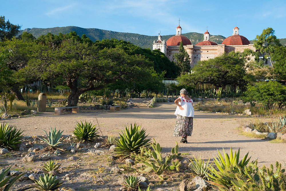 A Mexican woman walks on the grounds of the important Mesoamerican archeological site in Mitla, in the state of Oaxaca. The Church of San Pablo is visible in the background. (November 3, 2014)