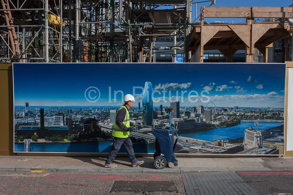 A workman pushes a dustcart walks past a billboard showing the future skyline of London, including the new 1, Blackfriars which will be a 52-storey tower 170m. on 6th October 2016, in London, England.