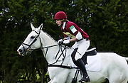 Young man rides a grey mare horse in an eventing competition, United Kingdom
