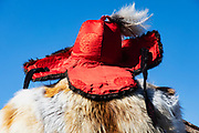 Portrait of Kazakh eagle hunter wearing his red hunting hat from behind, Altai Mountains, Bayan Ulgii, Mongolia