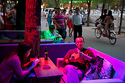 People having an evening drink at a bar in Shichahai, aka Houhai, which is Beijing's newly developed old town of nightlife, full of small bars and pubs. With the glow of lights it takes on an unreal feeling. Most cafes and restaurants are individually owned and have their own unique style.