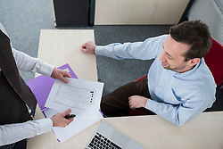 Two men office meeting desk holiday plan