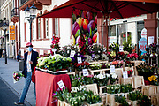A woman who just bought flowers in a shopping street in Bad Homburg is wearing a face mask. Bad Homburg is a spa city close to the Taunus mountain range.