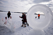 """Admirers wander past the Ice Garden in process by artists Peter Schulze and Lisa Carlson (not in photo) at the Art Shanty Projects on White Bear Lake. Schulze and Carlson """"glue"""" frozen shapes together with liquid water in freezing temperatures, documenting the sculpture's progress with time lapse photography. For color, they brought beet juice to dye certain ice forms."""