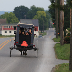 Ronks, PA, USA / June 16, 2011: An Amish family uses a traditional buggy to travel on a road in rural Lancaster County, Amish children look out of the rear of the horse-drawn buggy.